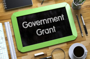 """Government Grant"" sign on desk"
